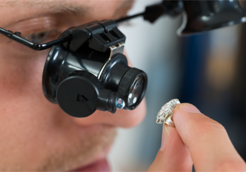 jeweler looking at diamond with loupe