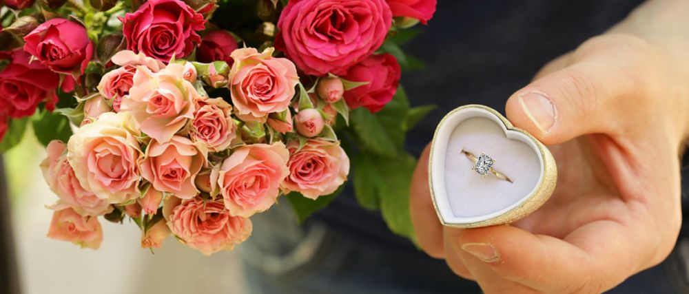 man holding a radiant cut engagement ring and flowers
